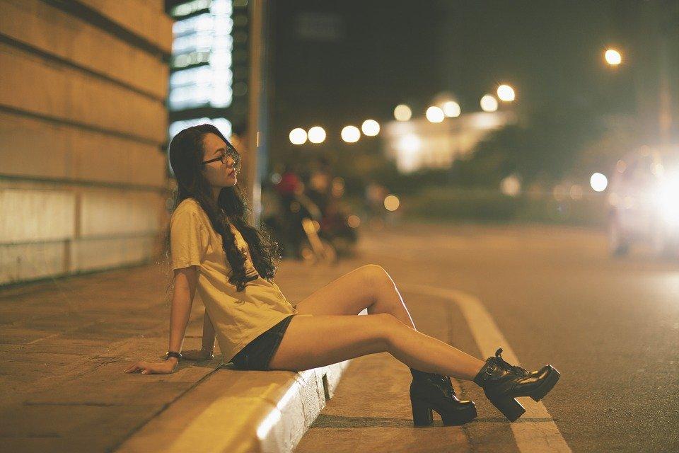 Foto de menina Tumblr sentada na calçada com os pés na avenida em quanto passa carros