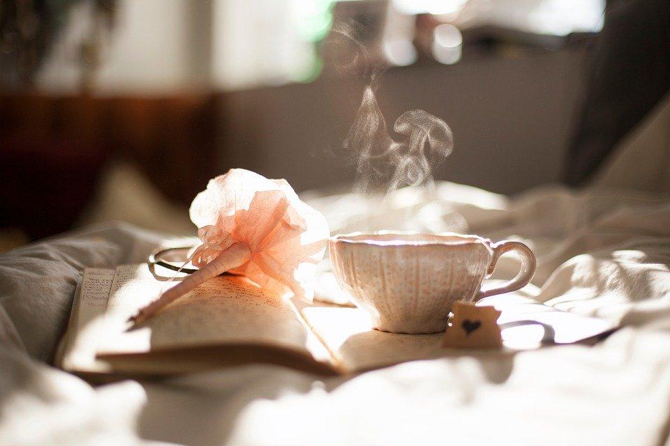 Foto Tumblr de um livro na cama com uma caneta em formato de rosa e uma xícara de café ou chá quente