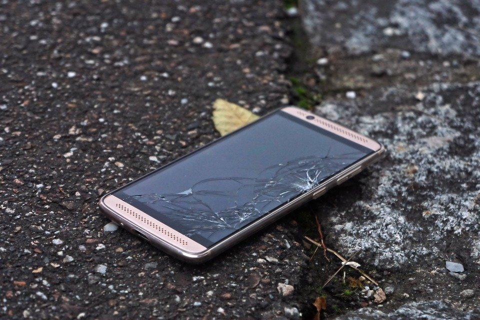 Imagem de celular caído no chão e com a tela quebrada