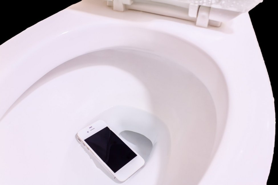 Imagem de celular caído no vazo sanitário privada com água ou xixi