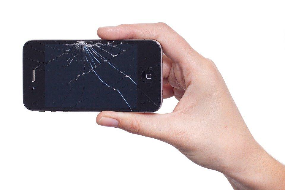 Imagem de mão segurando e mostrando um celular que caiu e quebrou a tela