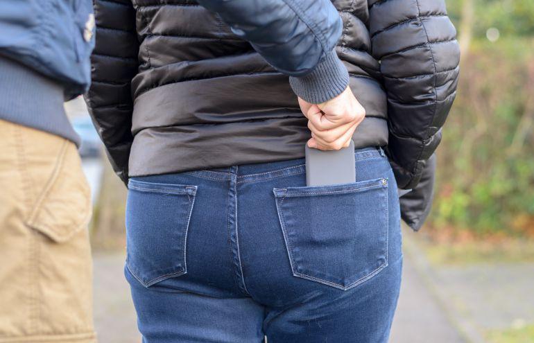 Imagem de celular sendo roubado no bolso de trás de uma calça feminina